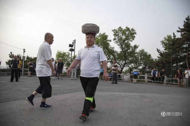 Chinese man has been walking with a 40kg rock on his head for four years to lose weight