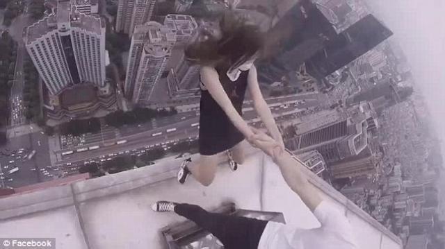 Terrifying video of pair performing stunts atop skyscraper