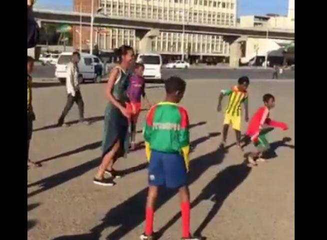 Model Liya Kebede playing street soccer with Ethiopian teenage children